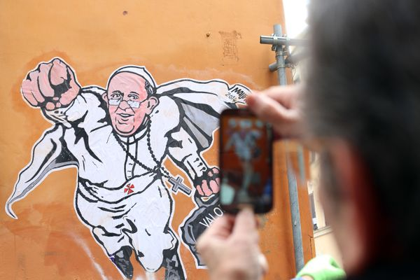 ROME, ITALY - JANUARY 29:  A man takes a picture with his smartphone of a graffiti featuring a 'superhero' version of Pope Fr