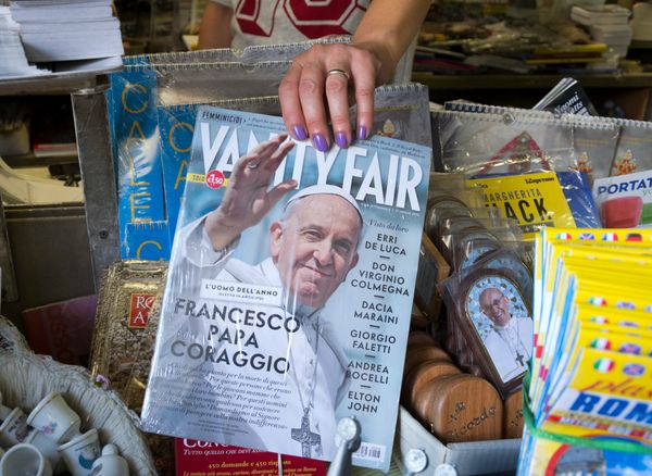 """A woman shows the cover of the Italian edition of Vanity Fair magazine, dedicated to Pope Francis, whom they elected """"Man of"""