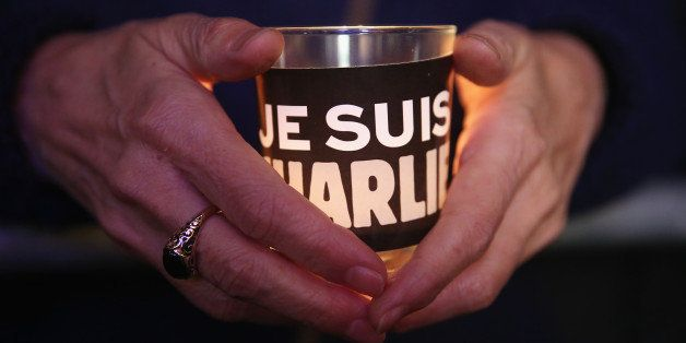 BERLIN, GERMANY - JANUARY 13:  People hold candles with 'Je suis Charlie' written on them as they attend a vigil organized by