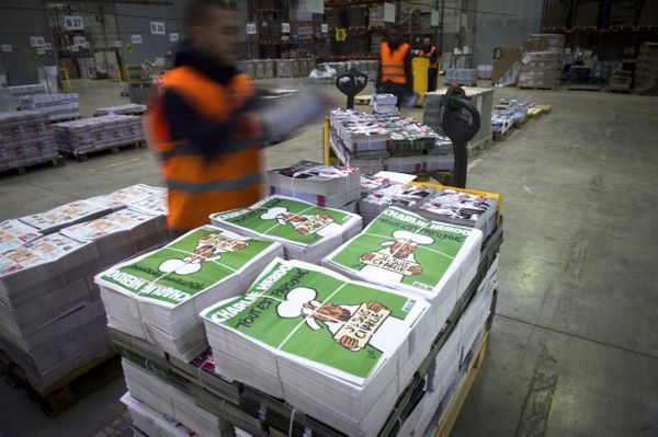 Employees check the arrival of the forthcoming edition of the weekly newspaper Charlie Hebdo, on January 13, 2015 in Villabe,