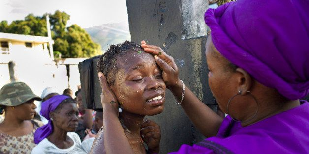 PORT-AU-PRINCE, HAITI - NOVEMBER 1, 2010: A Vodou priestess, or mambo, baths a young woman to facilitate her passage into the