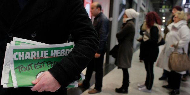 A man leaves after buying Charlie Hebdo newspapers as people queue at a newsstand in Paris, Wednesday, Jan. 14, 2015.  In an