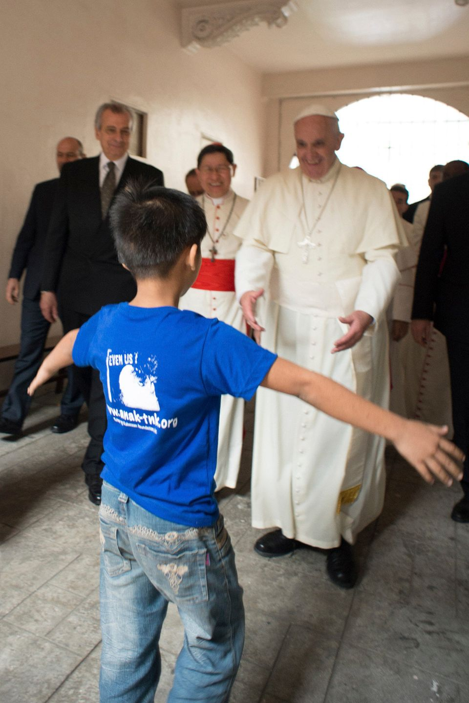 A young child comes in for a hug with Francis at the Anak-Tnk Foundation in Manila.