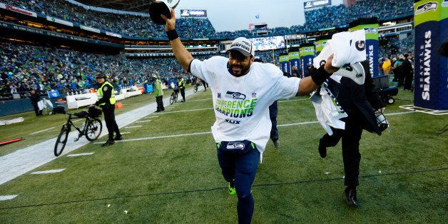 SEATTLE, WA - JANUARY 18:  Russell Wilson #3 of the Seattle Seahawks holds up the George S. Halas trophy after the Seahawks 2