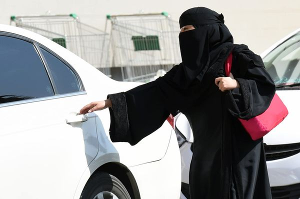 A Saudi woman gets into a taxi at a mall in Riyadh, because of the driving ban for women in Saudi Arabia