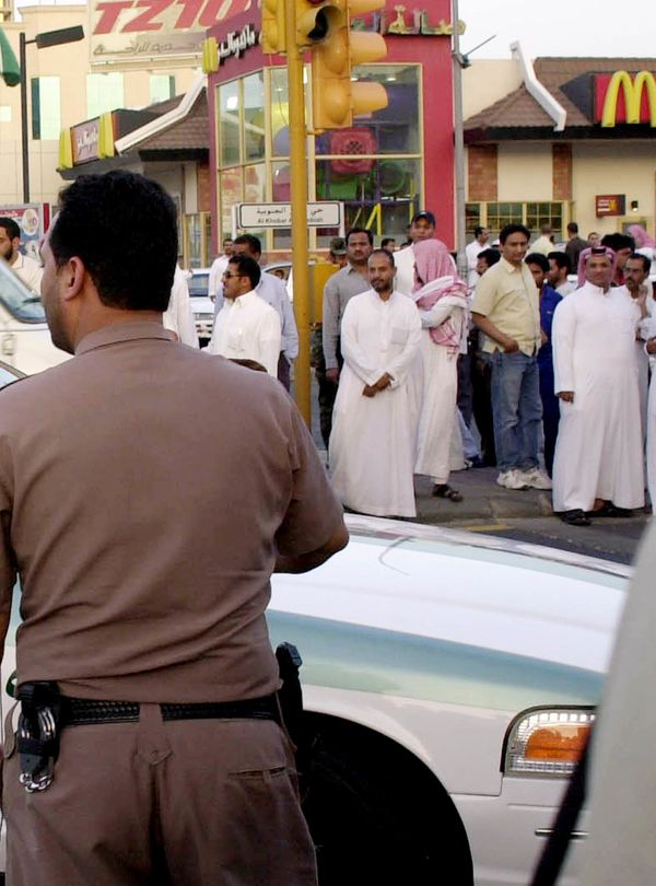 Saudis gather as police forces surround a mosque to hunt wanted militants, in Khobar, Saudi Arabia, after one-month amnesty,