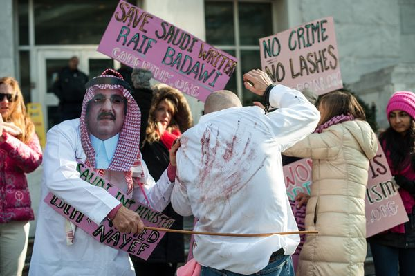 Protesters simulate a flogging in front of the Saudi embassy during a demonstration against the 10-year prison sentence and 1
