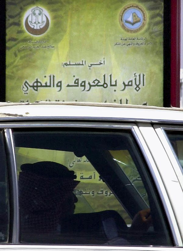 A Saudi driver stops in front of a billboard bearing logos of the Commission for the Promotion of Virtue and Prevention of Vi