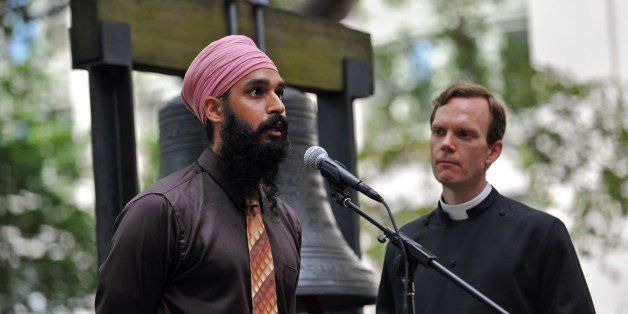 Simran Jeet Singh (L) of the Sikh Coalition speaks as the Reverend Matthew Heyd (R) of Trinity Wall Street listens before they ring the 'Bell of Hope' for the victims of the Sikh temple attack in Wisconsin in the courtyard of St. Paul's Chapel in New York on August 10, 2012. The bell was a gift from London to New York and is sounded for victims of terrible attacks and terrorism. AFP PHOTO/Stan HONDA (Photo credit should read STAN HONDA/AFP/GettyImages)