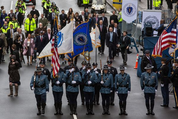 Police officers carry flags during wreath-laying ceremony.