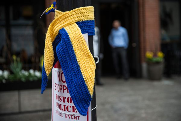 A knitted tribute hangs on a street light along the course of the Boston Marathon.
