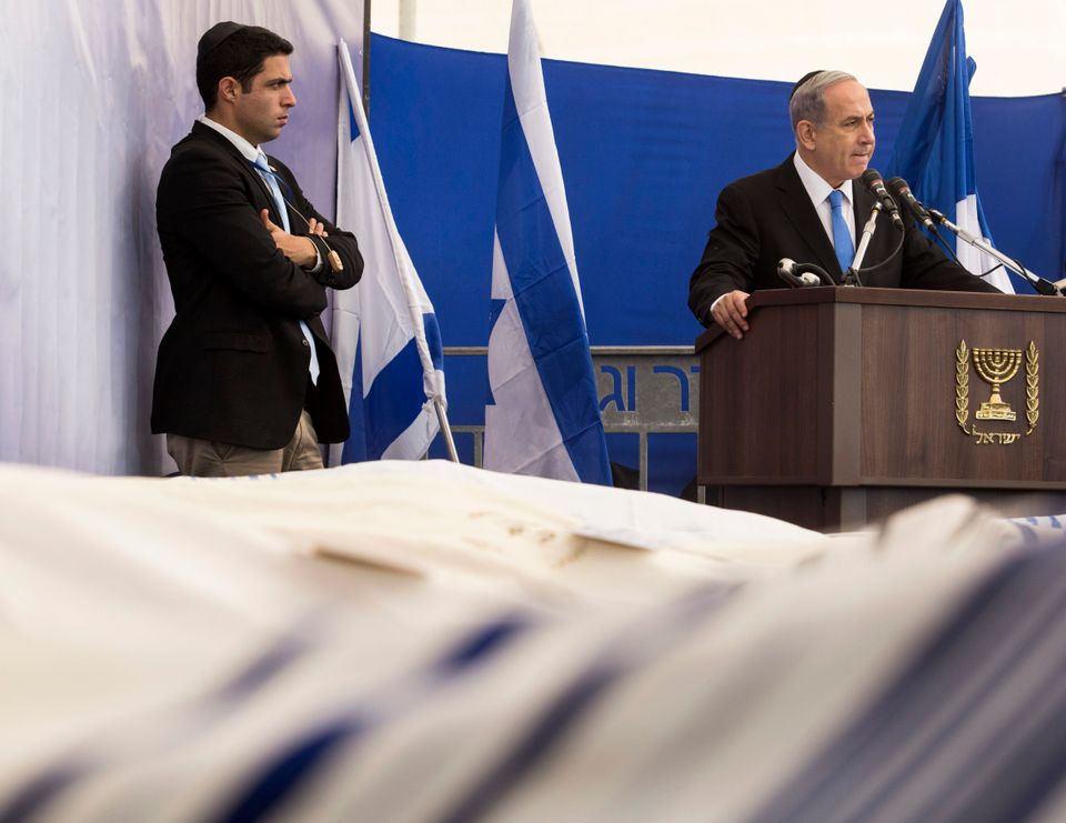 Israeli Prime Minister Benjamin Netanyahu delivers his eulogy behind the four  bodies, covered in prayer shawls, of the Jews