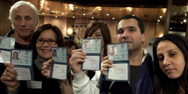 TO GO WITH AFP STORY BY MICHAEL BLUM A group of French Jewish immigrants to Israel show their new Israeli ID cards during a w