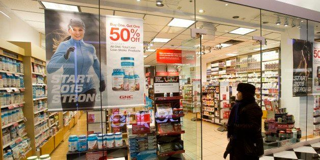A woman walks past a GNC store, Tuesday, Feb. 3, 2015 in New York. Numerous store brand supplements aren't what their label