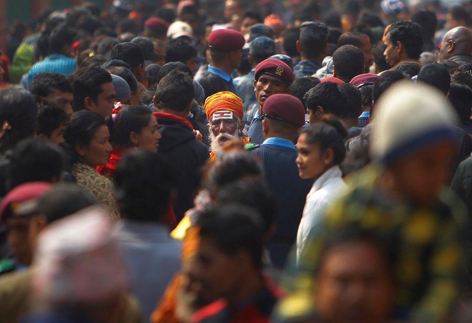 A Hindu holy man walks amid a sea of devotees at the Pashupatinath temple during Shivratri festival in Kathmandu, Nepal, Tues