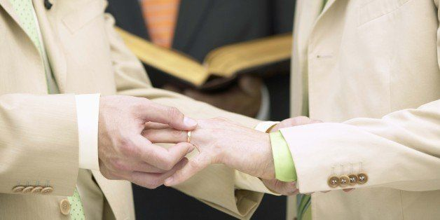 Man placing ring on another man's finger