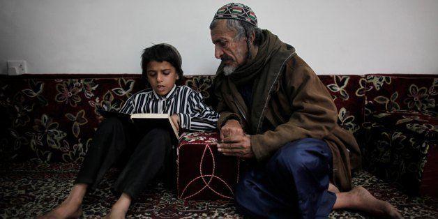 SANA'A, YEMEN - JANUARY 20:  Nine-year-old Yemeni Jew Salim Moussa reads the Torah with Yusuf Moussa Salim inside a protected