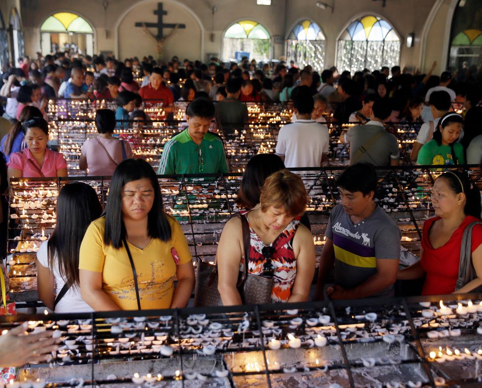 With their foreheads marked with ash, Catholic devotees pray after lighting candles in observance of Ash Wednesday at The Red