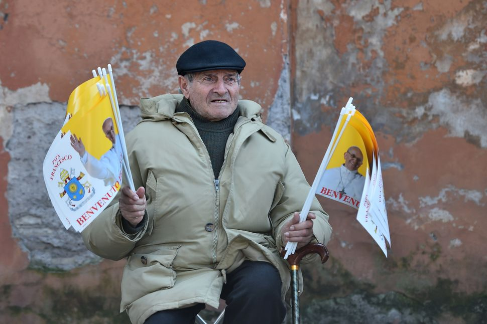 A man sells Vatican's flags outside the Santa Sabina church before the Ash Wednesday mass opening Lent, the forty-day period