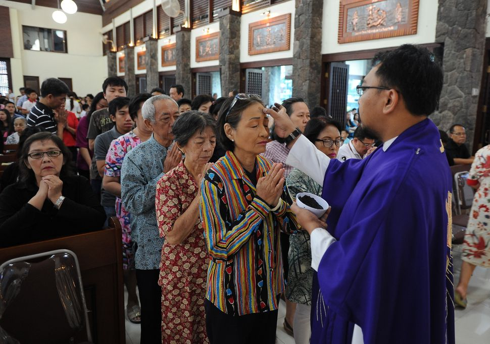 SURABAYA, INDONESIA - FEBRUARY 18: A Catholic devotee receives a cross mark with ash on her forehead during Ash Wednesday Mas