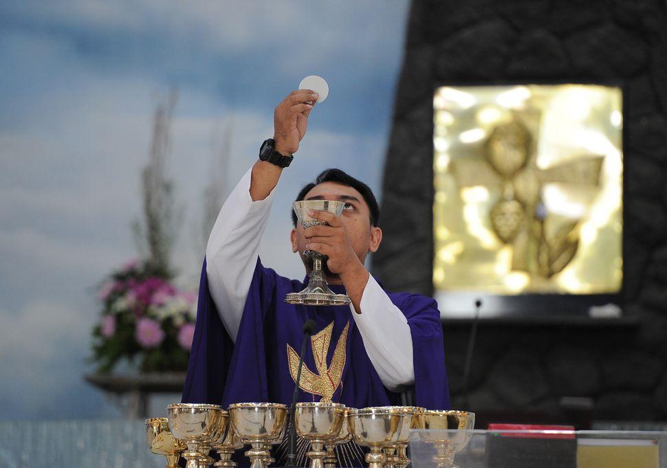 SURABAYA, INDONESIA - FEBRUARY 18:  Priest Aloysius Widyawan, RD leads the Ash Wednesday Mass at Roh Kudus Church on February