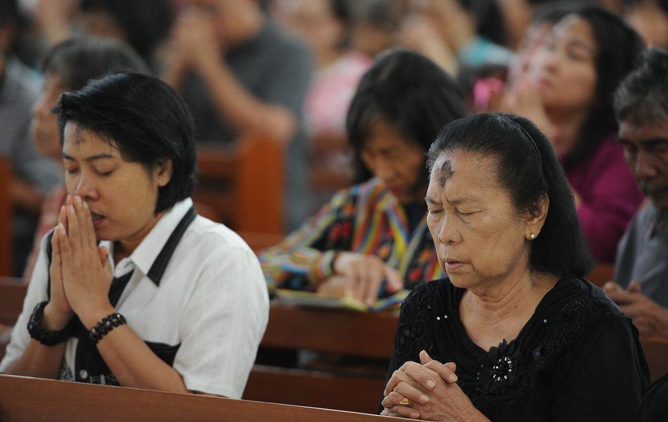 SURABAYA, INDONESIA - FEBRUARY 18:  Catholic devotees pray during Ash Wednesday Mass at Roh Kudus Church on February 18, 2015
