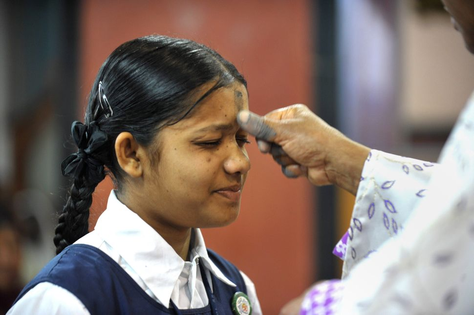 Indian Archbishop of Hyderabad Thumma Bala (R) marks the symbol of the cross with ash on the forehead of a young Christian de