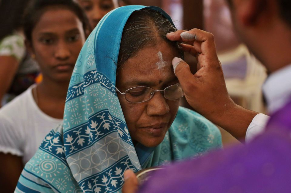 An Indian Catholic priest marks cross symbol on the forehead of devotees during an Ash Wednesday service at the St. Joseph Ca