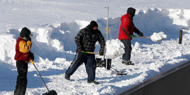 Workers clear snow from a roof in Boston, Monday, Feb. 16, 2015. New England remained bitterly cold Monday after the region's