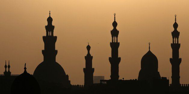 Birds fly over minaret's of mosques in Cairo on November 8, 2014. AFP PHOTO / MOHAMED EL-SHAHED        (Photo credit should r