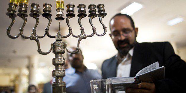 Iranian Jewish Rabbi Younes Hamami Lalehzar reads prayers after lighting candles to mark Hanukkah, the festival of lights, at