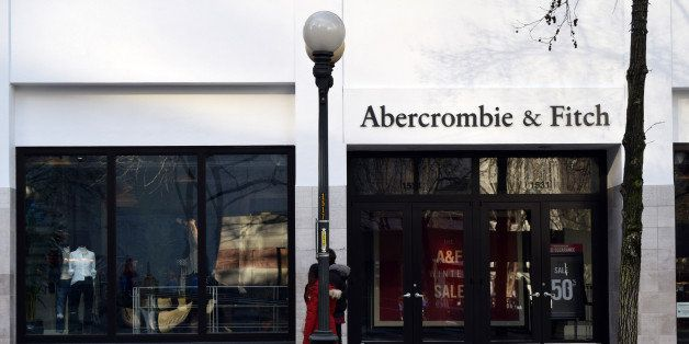 An Abercrombie & Fitch storefront and sign in downtown Seattle, Washington. Pedestrians and lamp posts are on the sidewalk ou