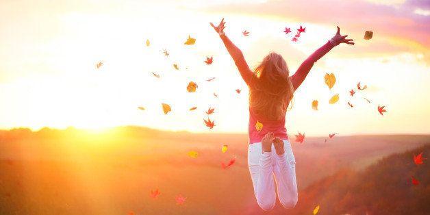 Woman jumping in the countryside at sunset with autumn leaves in the air.