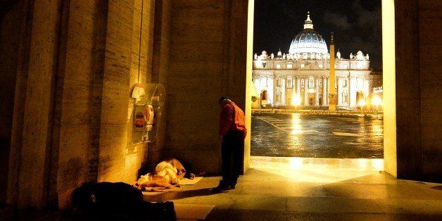 A volunteer of the Italian association 'City Angels' speaks with a homeless at the Vatican on November 18, 2014. City Angels