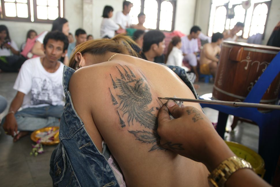 A Thai Buddhist artist draws a traditional tattoo on the back of a devotee during the tattoo festival at the Wat Bang Phra Te