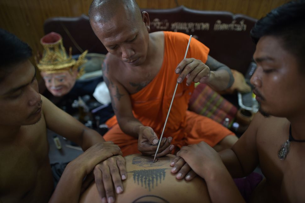 A Buddhist devotee receives a protective tattoo during the annual festival at Wat Bang Phra temple in Nakhon Chaisi, west of