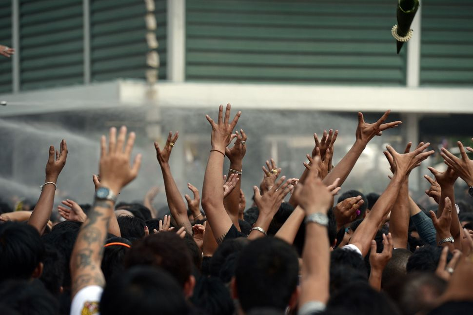 Devotees raise their hands to try and catch blessed objects during an annual tattoo festival at Wat Bang Phra temple in Nakho