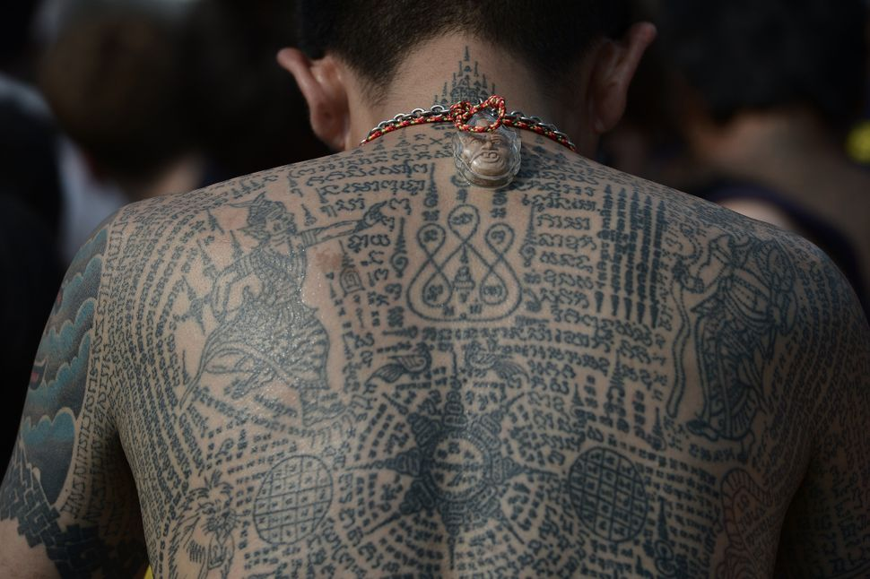 A heavily tattooed Buddhist devotee sits among the crowd during an annual tattoo festival, at Wat Bang Phra temple.