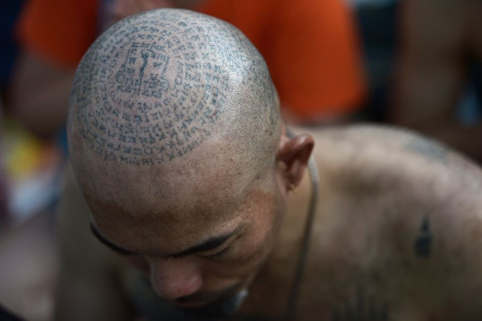 A Buddhist devotee works himself into a trance during the annual tattoo festival at Wat Bang Phra temple.