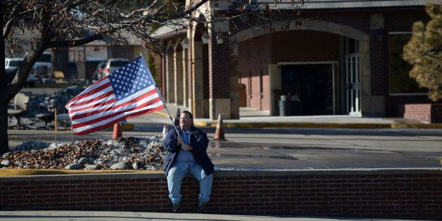 LAKEWOOD, CO - JANUARY 14: A New Hope Ministries, Center of Hope program participant waves an American Flag, trying to lure d