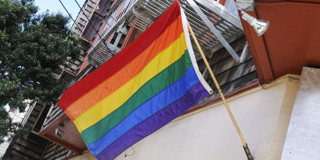 'This is a horizontal, color photograph of a Rainbow Flag in San Francisco's Castro neighborhood. There is slight motion blur