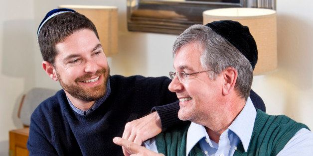 Senior Jewish man and adult son celebrating Hanukkah