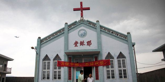 In this photo taken July 15, 2014, Pastor Tao Chongyin, left, speaks with church member Fan Liang'an in front of the Wuxi Chr