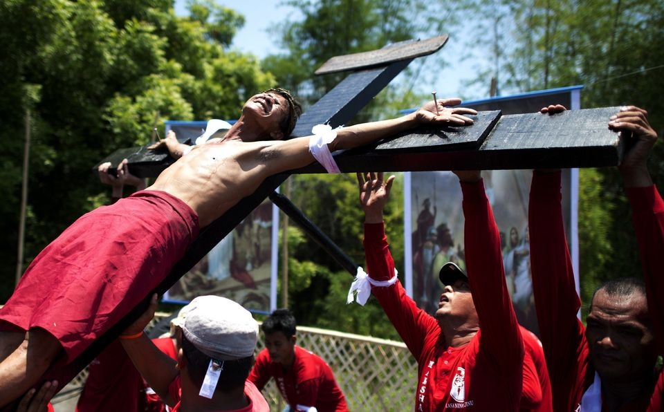 A Filipino Roman Catholic devotee grimaces in pain as he is nailed and being brought down on a cross during the a re-enactmen