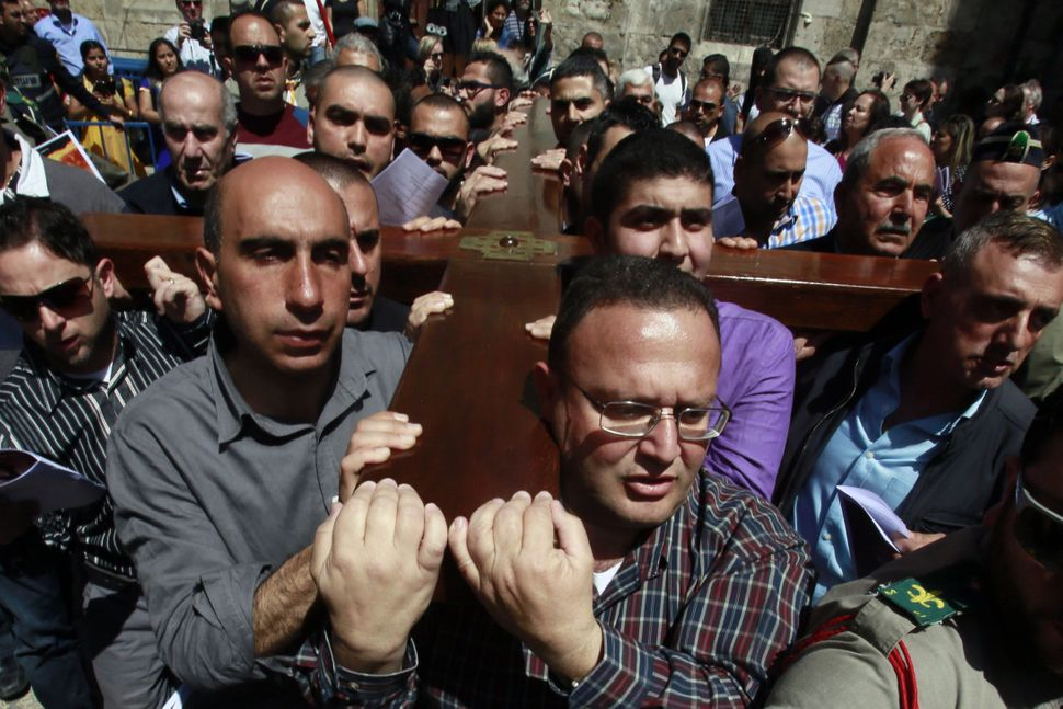 Catholic worshippers of the local parish carry a wooden cross along the Via Dolorosa (Way of Suffering) in Jerusalem's Old Ci