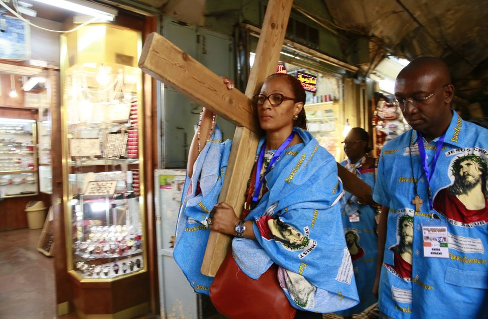 Catholic pilgrims carry a wooden cross along the Via Dolorosa (Way of Suffering) in Jerusalem's Old City during the Good Frid