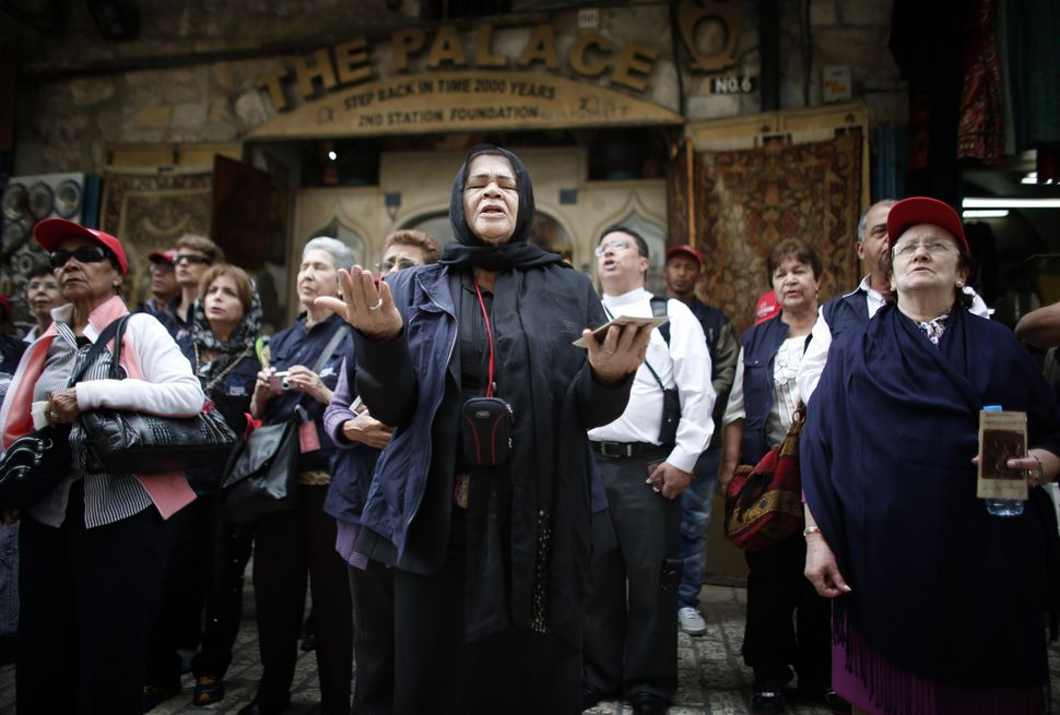 Catholic worshipers pray near the first station during the Good Friday procession along the Via Dolorosa (Way of Suffering) o