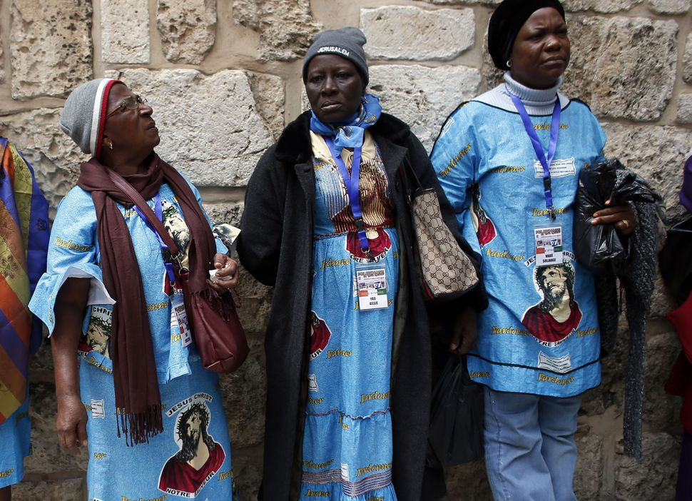 Catholic worshipers from Ivory Coast attend the ceremony at the Holy Sepulchre during the Good Friday procession along the Vi