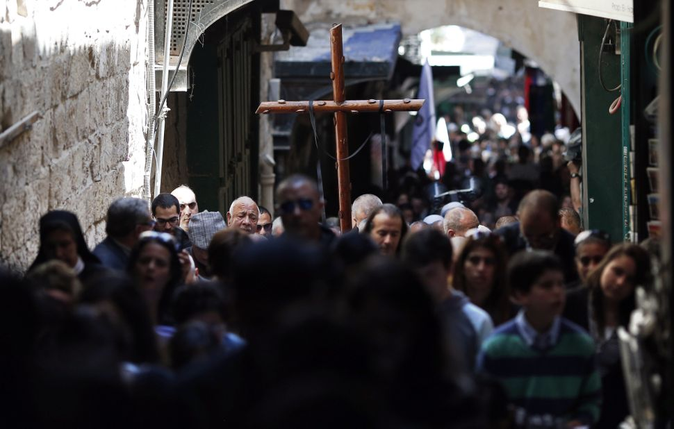 Catholic worshipers carry a wooden cross during the Good Friday procession along the Via Dolorosa (Way of Suffering) on April