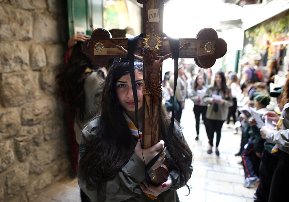 A Palestinian Catholic worshiper holds a cross during the Good Friday procession along the Via Dolorosa (Way of Suffering) on